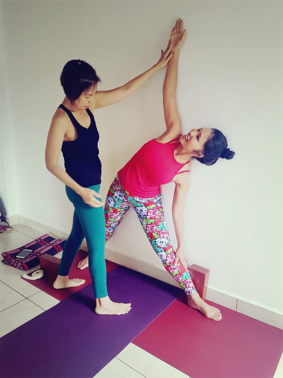 Our trainer Maki helping student to do yoga Pose